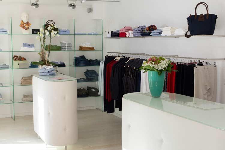 Die untere Etage der Modeboutique. Zu sehen sind die gepolsterten Verkaufstresen, Glasregale, …