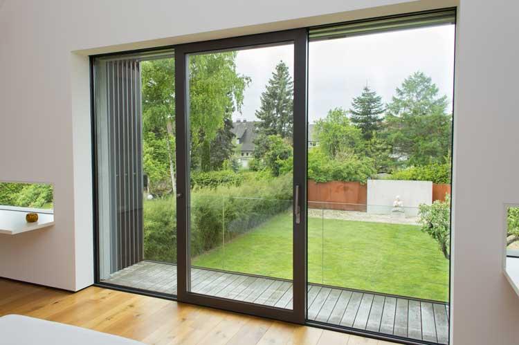 Balkonanbau aus Edelstahl. Die Brüstung aus Glas gibt den Blick in den Garten frei.